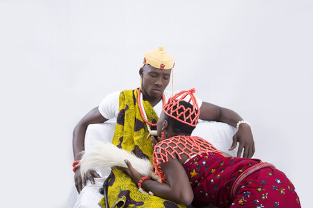 kneeling woman: Young woman kneeling in front of her man wearing traditional attire Stock Photo