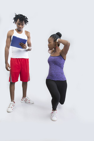 white singlet: Fitness trainer checking fitness plan with young woman doing exercise  Stock Photo