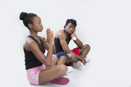 A young lady meditating with her legs crossed and a man sitting and looking at her photo