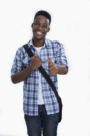 thumps up: A young boy carrying a bag with a thumps up sign  Stock Photo