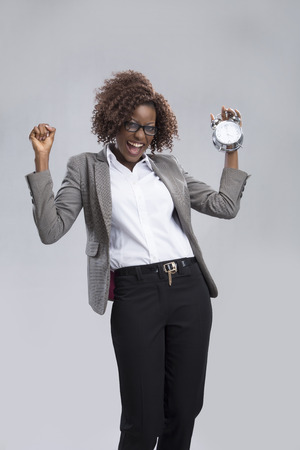 portrait of a businesswoman holding an alarm clock smiling and expressing excitement.  photo