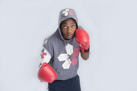 hooded top: A young boy in hooded top wearing a boxing gloves on isolated background