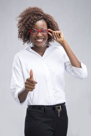 Businesswoman holding glasses and doing the thumbs up photo