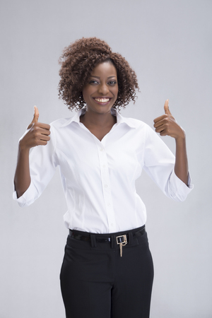 portrait of a businesswoman smiling and doing the thumbs up sign. photo