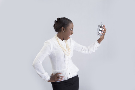 25 29 years: Businesswoman looking at alarm clock with hand akimbo