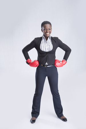 akimbo: Businesswoman with her arm akimbo giving a cute smile Stock Photo