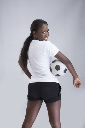 akimbo: A rear view of a young woman holding a football and left arm at akimbo.
