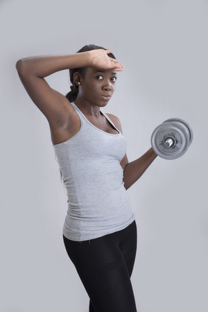 hand on forehead: A young woman holding a dumbbell with hand on forehead