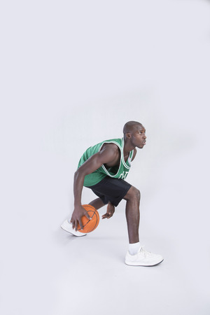 dribbling: A young basketball player dribbling on isolated background
