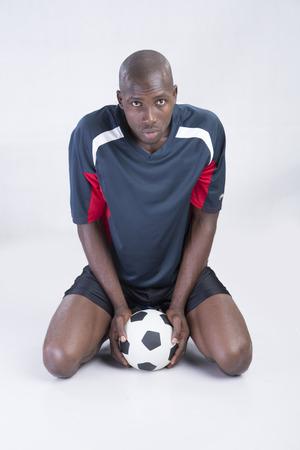 man kneeling: A man kneeling with soccer ball in between legs