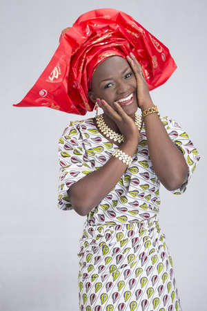 attire: Happy woman in traditional attire over a grey background