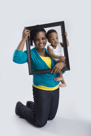 A beautiful woman kneeling and carrying her baby with a picture frame photo