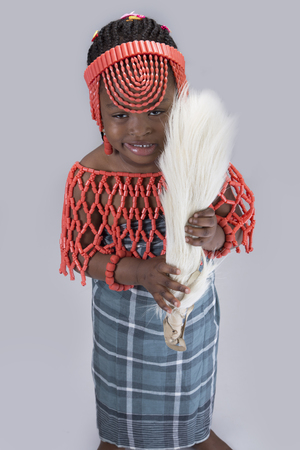 horse tail: A beautiful girl in native attire holding a horse tail standing over grey background