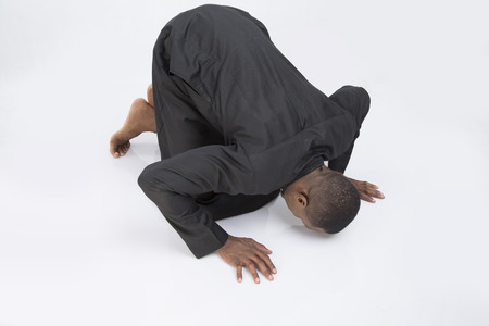 bowing head: Man bowing his head to the ground