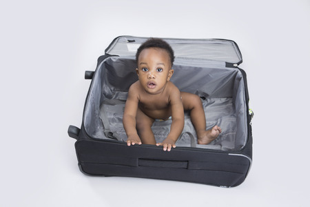 6 12 months: handsome baby boy sitting in a suitcase Stock Photo