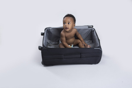 6 12 months: happy baby boy in a suitcase Stock Photo