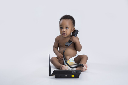 bare feet boys: Baby boy sitting on the floor holding a telephone