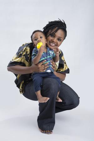 en cuclillas: Una hermosa mujer en cuclillas y llevando a su beb� en el regazo