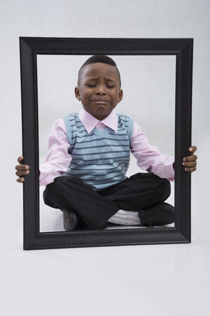 trouser legs: Little boy holding wooden picture frame looking sad