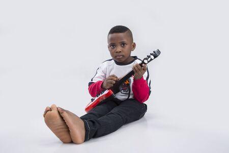 trouser legs: Cute little boy playing a guitar Stock Photo