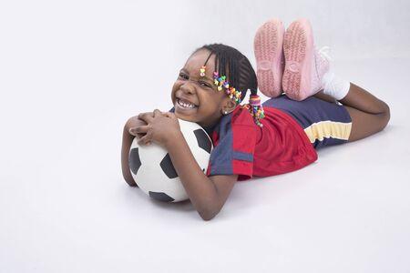girl lying down: Una chica joven que se acuesta y la celebraci�n de una pelota de f�tbol Foto de archivo