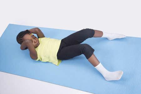 leggings: A little girl exercising on a gym mat on isolated background Stock Photo