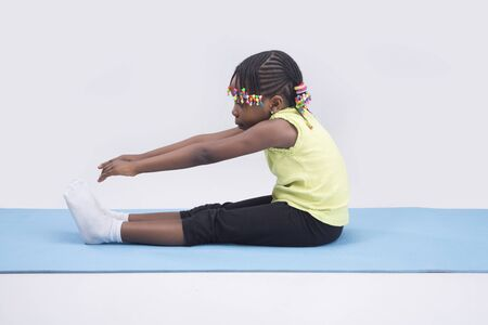 A little girl stretching on isolated background Stock Photo