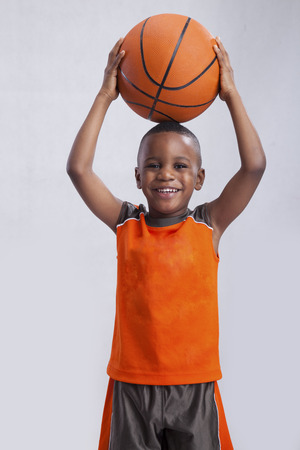 Little boy with basketball on his head photo