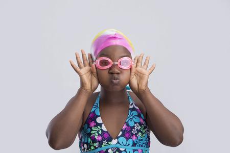 puffed cheeks: Cute little girl in swimwear puffing her cheeks