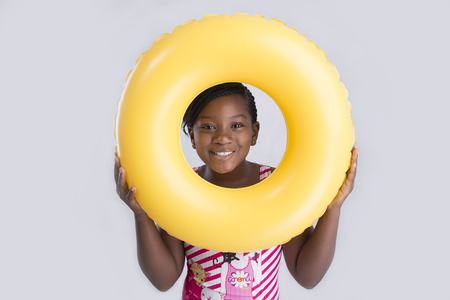 between 5 and 10 years: Cute little girl looking through a swim float  Stock Photo