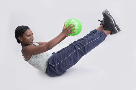 rubber ball: Beautiful little girl holding rubber ball while working out