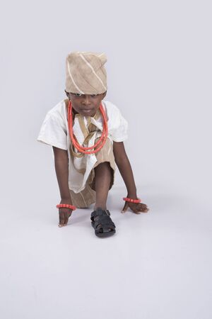 knee bend: kid traditionally dressed kneeing with hands on the floor Stock Photo