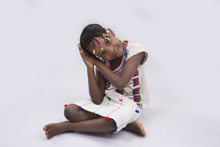 attire: kid dressed in Fulani attire sitting on the floor with hands akimbo