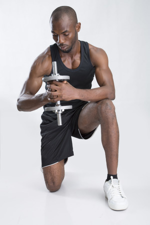 kneel down: A young man holding a dumbbell Stock Photo