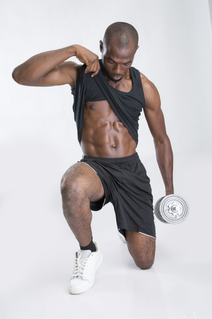 sleeveless top: A young man holding a dumbbell with one hand and lifting up sleeveless top with the other hand