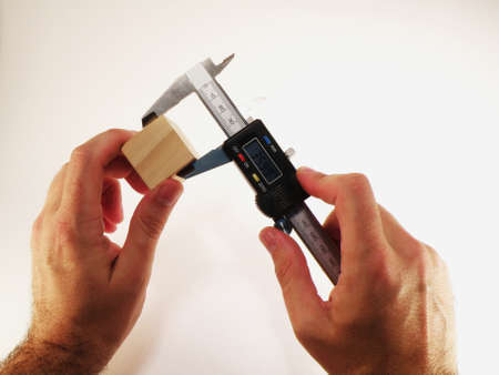 marquetry: precision measuring hand with the wood Stock Photo