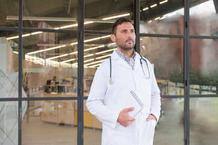 knappe dokter in een technisch medisch centrum met een bezorgd grin Stockfoto