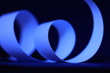 paper curl: A graphic blue paper curl on a black background