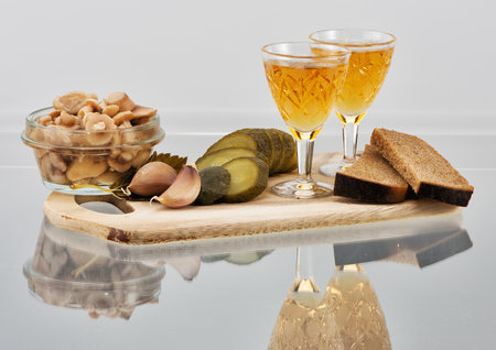 sobriety: Two short glasses of whisky, bread, marinaded mushrooms and cucumber on a wooden board