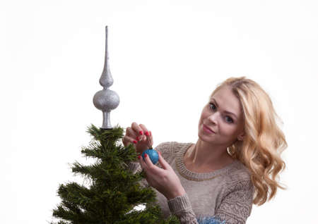 decorates: Beautiful young blonde girl decorates the Christmas tree Stock Photo