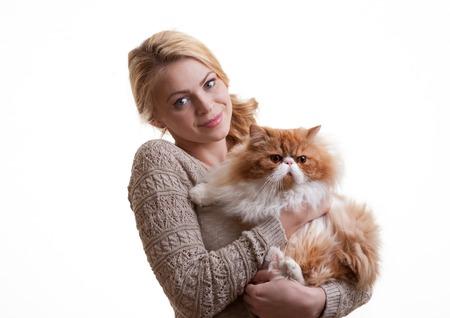 Молодой симпатичная девушка имеет красный персидский кот на руках