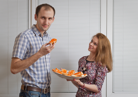 adult sandwich: The nice girl with a plate of sandwiches with red caviar treats the young man Stock Photo