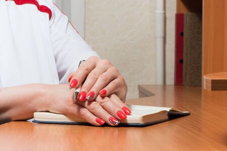 female hands: Female hands with manicure over pages of a notebook hold a pen