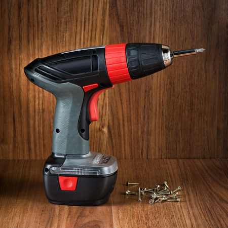 power operated: The electric tool for twisting of screws against wooden texture Stock Photo