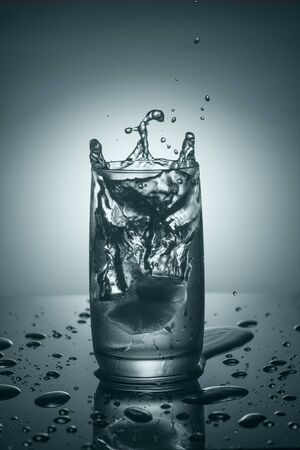 purified: Splashes in a glass of pure cold water with an ice cube