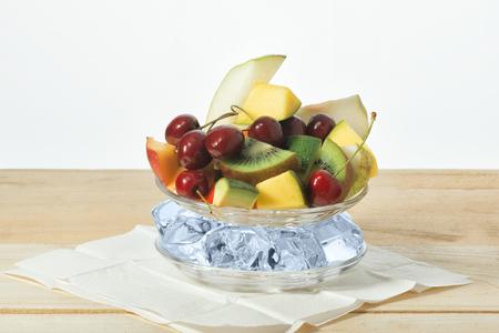 Ломтики фруктов, черешня на тарелке со льдом на поверхности из деревянных досок