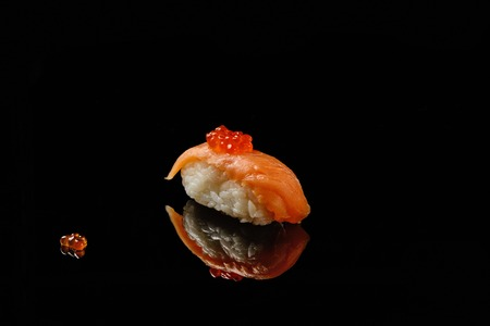 acryle: Sushi and red caviar of salmons on black acryle with reflection Stock Photo