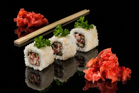 cuisine entertainment: White beaters, wooden sticks for sushi and ginger on black acryle with reflection Stock Photo