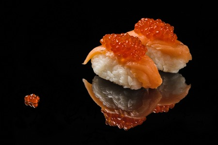 acryle: Sushi and red caviar on black acryle with reflection