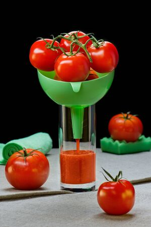 Tomatoes in a funnel in a glass with tomato juice on a table